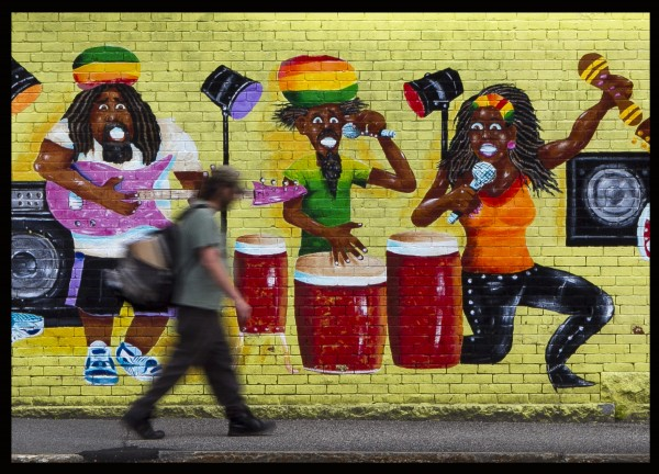 In a mural on the wall, musicians wearing Rastafarian headwear appear to take notice of a pedestrian on Cedar Street outside the Lewiston Pawn Shop last month.