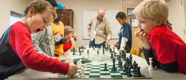 First-time chess player Braden Lamb, left, enthusiastically plays an early move against a more seasoned player, third-grader Nathan Dooley, during an after-school chess program at Fred P. Hall Elementary School. Ben Monaghan, center, of the Maine Chess Academy, is seeking to expand the group's work through a fundraising drive on Kickstarter.