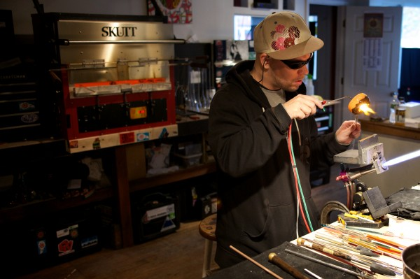 Glass artist Brian Owoc works on one of his signature, doughnut-shaped pipes in Portland Thursday morning. Before becoming a fill-time artist, Owoc was a doughnut baker.
