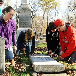 Monmouth social studies teacher Jocelyn Gray, second from left, helps students, from left, Kelsea Blanton, 14; Rebecca Bero, 15; Duncan Grant, 15; and Jordhan Coward, 14, dig a trench around a toppled headstone that will eventually be righted in the Monmouth Center Cemetery recently. The students have been asked not to enter the cemetery without supervision of the cemetery's board.