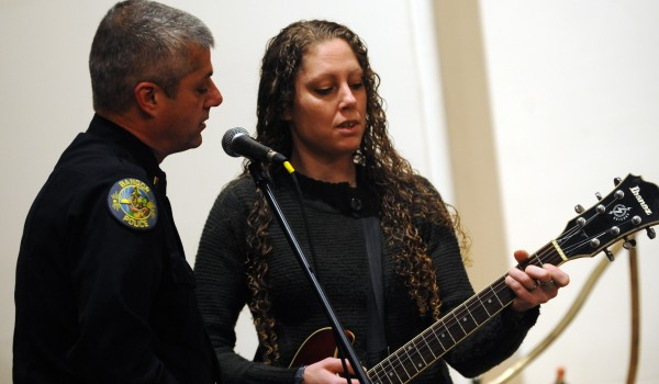 Shannon Denbow and Lt. Paul Edwards sing Bette Midler's &quotThe Rose&quot before the start of a vigil held on Saturday at the Hammond Street Congregational Church to honor the homeless people of Bangor who have died during the past year.