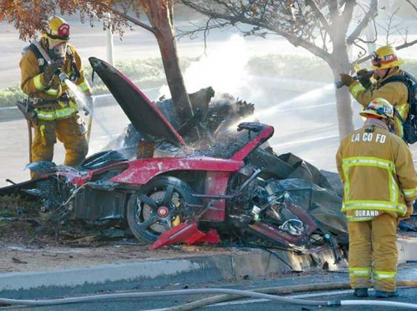 Firefighters extinguish the fire in the car where actor Paul Walker was killed along with Roger Rodas during a car crash in Valencia, Santa Clarita, Calif., Nov. 30, 2013.