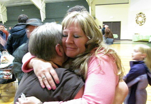 Joline Scovil, grandmother of a 3-year-old girl who was shot in the neck at her Bangor residence on Oct. 30, gets hugged by a well-wisher at a dinner held to raise money for the girl's family at Calvary Chapel Church's dining hall in Orrington on Saturday.