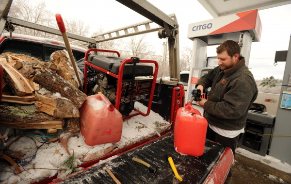 Mark Ebersole fills gas cans Tuesday at Trade Winds Marketplace in Eddington for his generator at his home in Clifton which is without power. Ebersole says he hopes to fix his neighbors' generator which is in the back of his truck so that they can stay warm too.