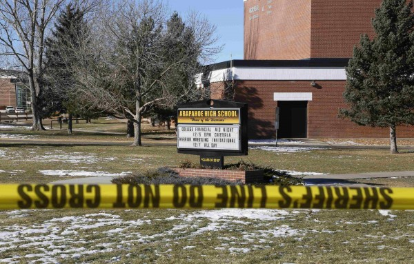 Police barricade tape surrounds Arapahoe High School a day after a shooting incident in Centennial, Colo., Dec. 14, 2013. Police were looking into the motive of a student who opened fire at the school on Dec. 13, severely wounding a teenager before apparently killing himself.