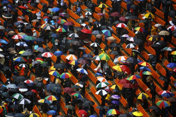 Mourners try to stay dry during the national memorial service for late former South African President Nelson Mandela in Johannesburg's National Bank Stadium Dec. 10, 2013.
