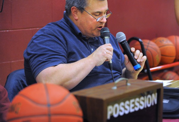 Bill Libby announces the lineups before the start of a basketball game at Orono High School. Libby has been announcer at the games for 15 years.