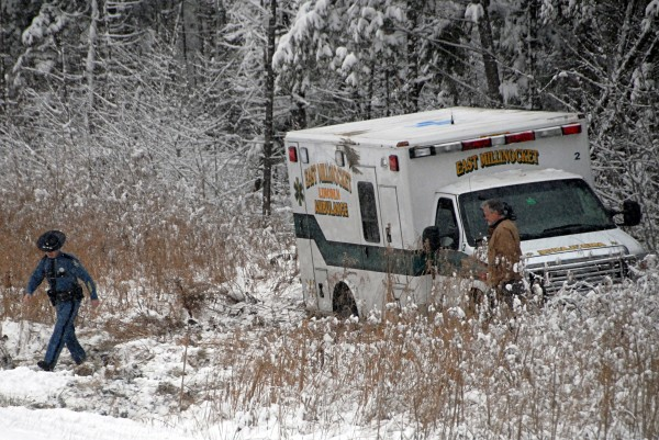 Maine State Police Trooper Trevor Snow walks away from an East Millinocket-Lincoln ambulance that rolled over while heading south on Interstate 95 on Monday.