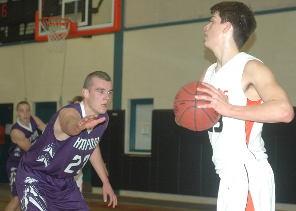 Hampden Academy's Zach Gilpin, left, guards Brunswick's Elliot Boyd during a KVAC boys high school basketball game at Brunswick on Friday. The Broncos won the clash of KVAC unbeatens with a 65-54 double overtime victory to improve to 3-0.