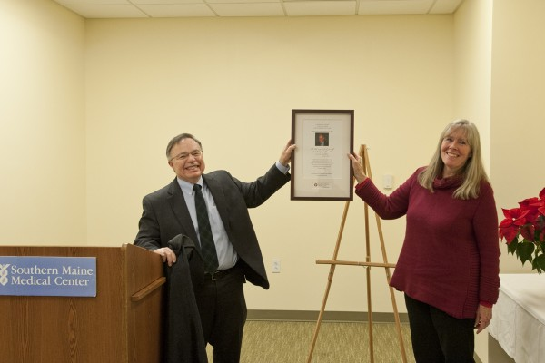 Southern Maine Medical Center (SMMC) president and CEO Ed McGeachey and Ruth Fernandez unveil the plaque with Dr. Robert Fernandez's photo and dedication which will soon be placed in the lobby of the Robert V. Fernandez, M.D. Medical Office Building at 9 Healthcare Drive in Biddeford. In addition, his name has been placed on the outside of the building.