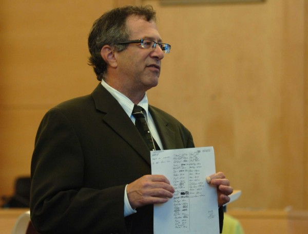 Defense attorney Jeffrey Silverstein displays a ledger containing which listed debts owed to murder victim Michael Miller Jr. during closing arguments in the trial of Miller's accused murderer, Nathaneal Nightingale, on May 31, 2011.