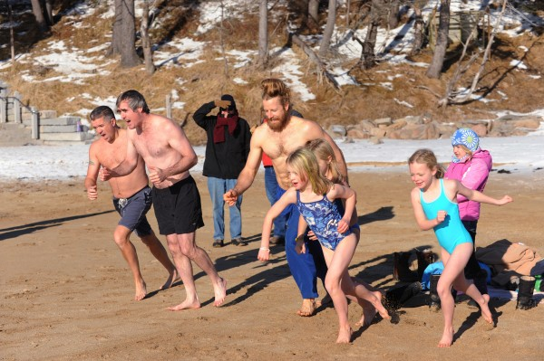 A small group of people charge down the beach for a polar dip in the waters off Sand Beach in Acadia National Park on Jan 1, 2014.