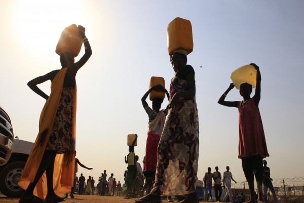 In this January 2014 file photo, displaced people carry water containers on their heads at Tomping camp. Some 15,000 displaced people who fled their homes from this camp are sheltered by the United Nations, near South Sudan's capital Juba.