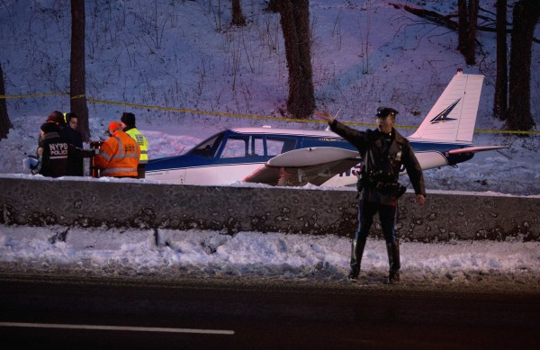 A single-engine plane is seen amid traffic on the Major Deegan Expressway in the Bronx borough of New York on Jan. 4, 2014. The small plane landed on the expressway on Saturday afternoon, according to the city's Office of Emergency Management, local news sources reported. Three people were taken to a nearby hospital for evaluation.