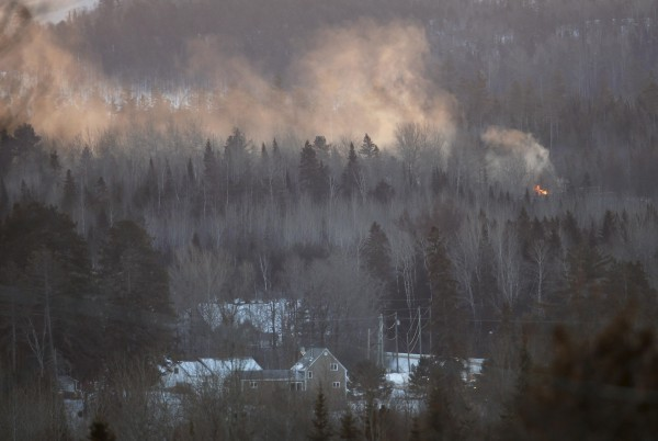 Flames and smoke are seen at the site of a train derailment in Wapske, New Brunswick, Jan. 8, 2014. A Canadian National Railway train carrying propane and crude oil derailed and caught fire on Tuesday in northwest New Brunswick, Canada, the latest in a string of train accidents that have put the surging crude-by-rail business under heavy scrutiny. No one was injured but about 45 nearby homes were evacuated.