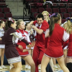 Martin Ward of Dexter (middle) dances along with several teammates and a Narraguagus competitor (left) after completion of the Eastern Maine Class C cheerleading championship Saturday at the Cross Insurance Center in Bangor.