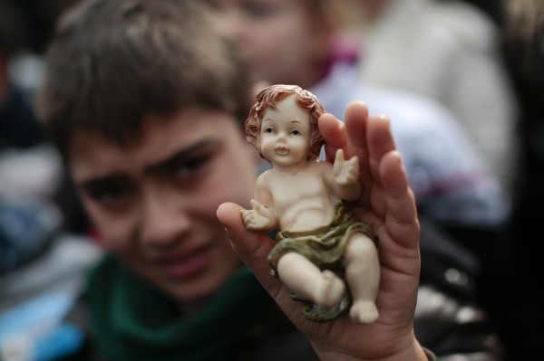 A child holds a figurine of Baby Jesus as Pope Francis leads the Sunday Angelus prayer in Saint Peter's Square at the Vatican Dec. 15, 2013.