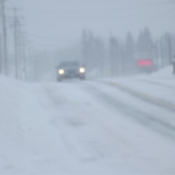 Blowing snow partly obscures a car traveling on U.S. Route 1 in Machias on Friday afternoon.