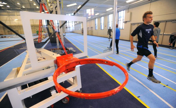 University of Maine track athletes warm up on the new track at the Field House in Orono Wednesday.