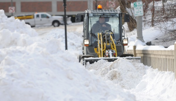 Snow removal equipment pushes snow along the sidewalk on Franklin Street in downtown Bangor on Sunday morning.