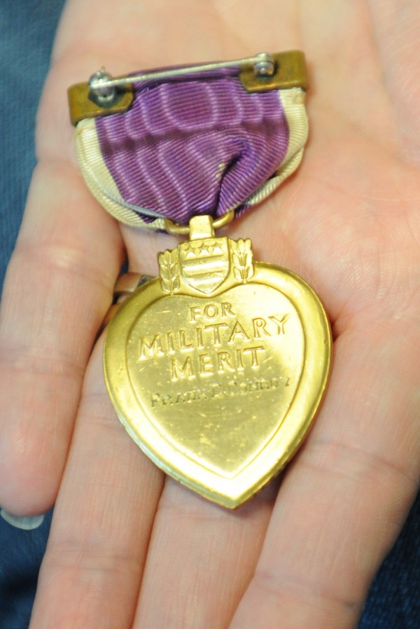 Monica Pollard proudly displays the Purple Heart medal with the name Frank Conroy engraved on the back that once belonged to her great-granduncle Frank Conroy. It was returned to her by Sheila Bedi who found it in a box of items acquired at an auction. Bedi and her family drove from Vershire, Vt., to Pollard's Pittsfield home to return the Purple Heart medal.
