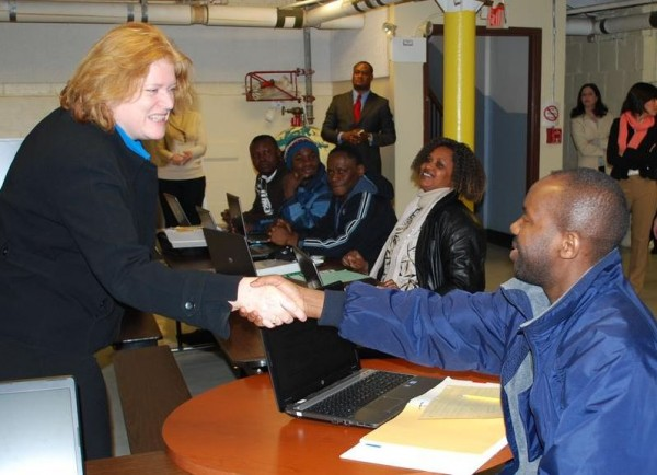 U.S. Assistant Secretary of State Anne Richard, left, greets Jean Pierre Gatarayiha on Feb. 21,during a class at Portland Adult Education. Gatarayiha, who immigrated from Rwanda six months ago, would like to become an environmental technician and is taking an eight-week course on entering the American labor market.