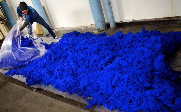 Alden Andrews bags loose wool at the Saco River Dyehouse in Biddeford on Tuesday. The color, one of over 400 offered, is called electric blue.