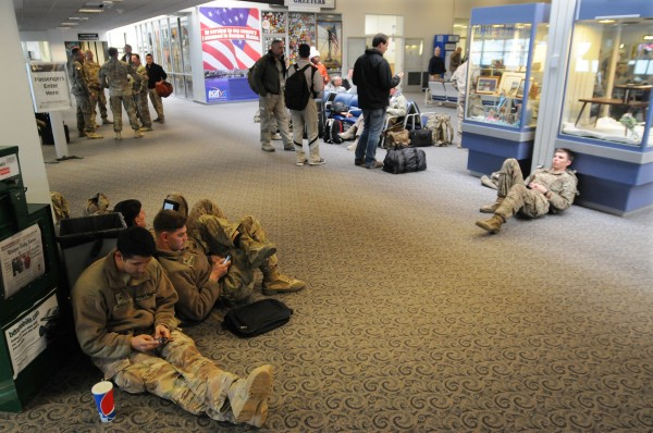 Members of the military sit and wait to board their flight at Bangor International Airport on Monday. The servicemen, including some 112 civilian contractors, were detained and had to spend the night after an alleged altercation between a contractor and a customs agent drew extra scrutiny of the troops' bags and gear.