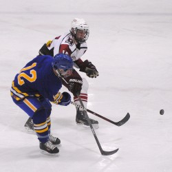 Falmouth High School's Andre Clement (left) and Bangor High School's Justin Courtney battle for the puck during their game on Feb. 3, at Sawyer Arena in Bangor.