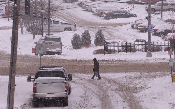 A man walks across an intersection in Bangor on Wednesday afternoon in the falling snow.