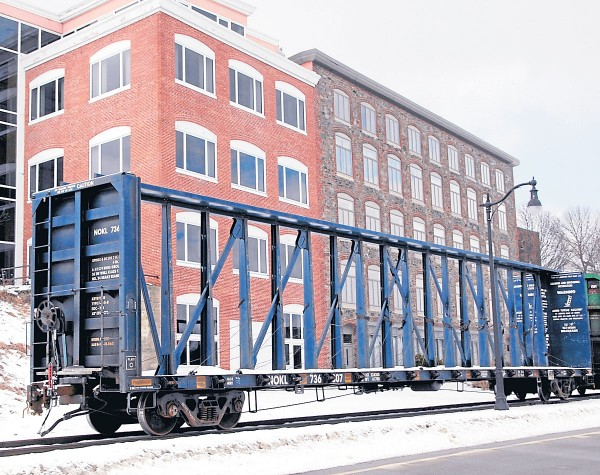 A rail car designed for carrying lumber products is the last car on a Pan Am Railways train moving north through Bangor on the afternoon of Feb. 10,