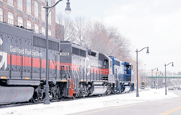 A Pan Am Railways locomotive and two Guilford Rail System locomotives are at the head of a train heading northbound along the Bangor waterfront on Feb. 10