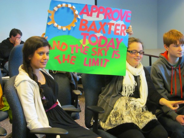 Nica Todd, 13, of Cumberland, left, and Brianna Keliehor, 13, of Gorham hold a sign in support of Portland's Baxter Academy charter school in April 2013 during a Maine Charter School Commission meeting in Augusta where the commission approved the school.