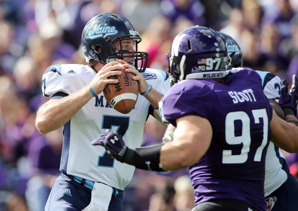 In this September 2013 file photo, Maine quarterback Marcus Wasilewski (left) looks for a receiver while pressured by Northwestern's Tyler Scott (right) during their game in Evanston, Ill.