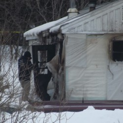 A state fire marshal investigator takes photographs of a mobile home that was heavily damaged by fire in Danforth on Friday morning.