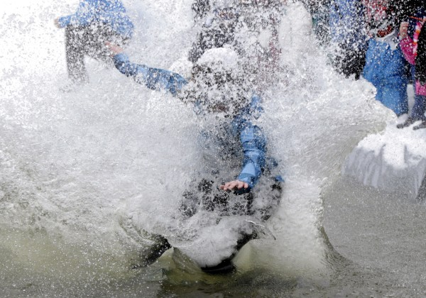 The snowboarder ends up crashing into the pond during the Slush Cup at Shawnee Peak on Saturday.