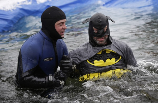 A pond skimming participant in a Batman costume is assisted getting back onto his feet after crashing during the Slush Cup at Shawnee Peak on Saturday.