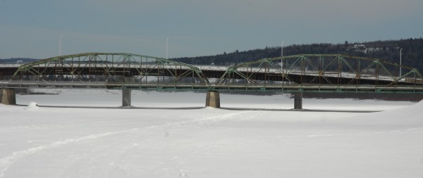 The frozen St. John River passes through Fort Kent and around the pilings of the old international bridge and the new bridge currently under construction.