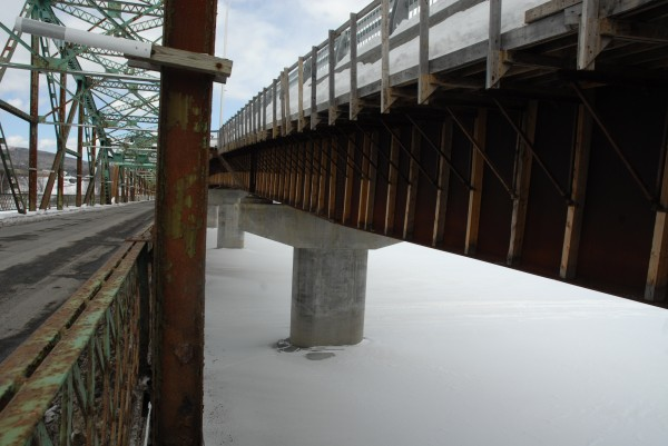 New pilings are visible through the rusty framework of the existing international bridge in Fort Kent connecting Maine to New Brunswick.