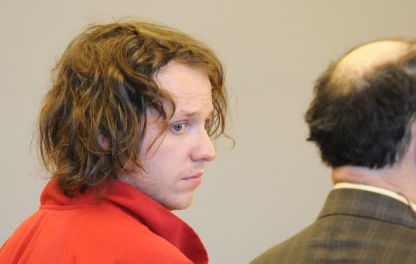 Samuel Moore, 25, of Bangor looks back at the media during his initial appearance in court at the Penobscot Judicial Center in Bangor March 7.