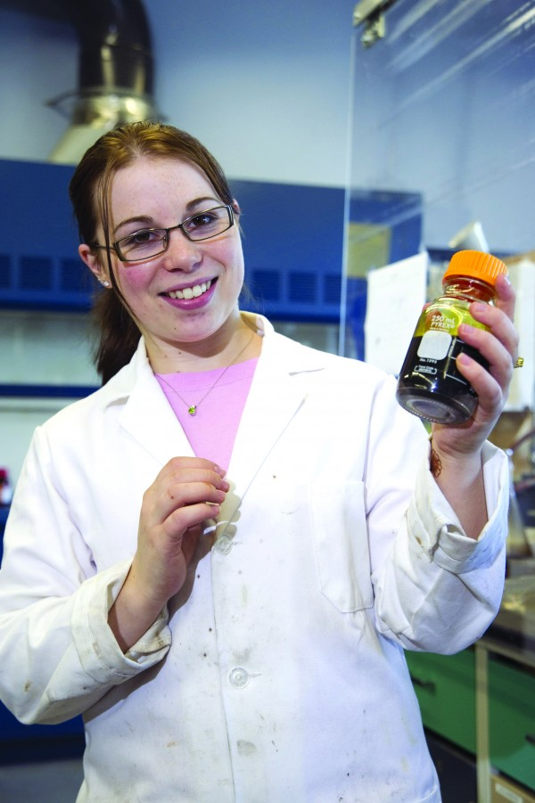 In late October 2011, Paige Case, a chemical engineering undergraduate student at the University of Maine, holds a container filled with biofuel oil made from cellulose in waste wood. The new process of creating biofuel was developed by UMaine professor Clayton Wheeler and his students.