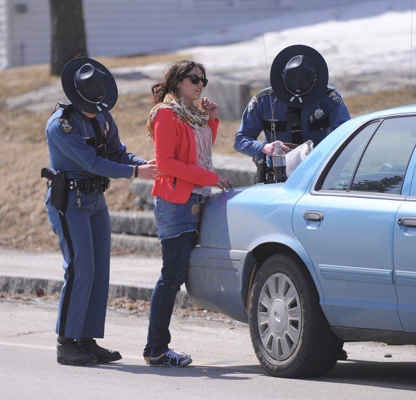Maranda McCafferty, the driver of a sedan that collided with a fuel delivery truck, is checked by Maine State Police Trooper Desiree Wuthenow (left) and Trooper Jeremiah Wesbrock in Winterport on Wednesday.
