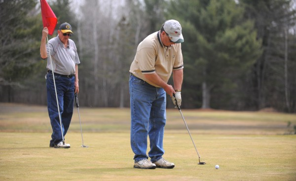 Dave Hayden (right) and Greg Black enjoy a round of golf at the Hermon Meadow Golf Club Tuesday morning. They said that this is their second time playing this spring.