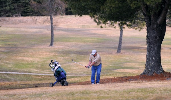 Dave Hayden chips onto a green while playing a round of golf at the Hermon Meadow Golf Club Tuesday morning.