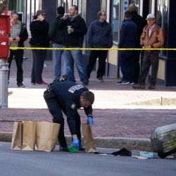 A police officer collects the contents of a trash can on Congress Street in Portland near a drug store robbery crime scene on April 11, 2014.