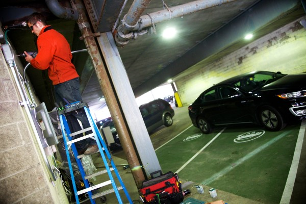 Electrician Jonathan Hebert installs wiring for a pair of electric car charging stations in Tim Soley's parking garage on Fore Street in Portland Thursday.