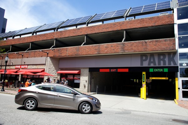 Solar panels face the sun atop Tim Soley's parking garage on Fore Street in Portland Thursday. Electricians are installing a pair of electric car charging stations this week.