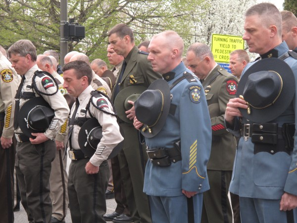 Law enforcement officers from several agencies hold their hats for a moment of silence to honor Officer Stephen Arkell of Brentwood, New Hampshire, who was killed in action Monday. The officers were at the Maine Law Enforcement Officers Memorial in Augusta for an annual remembrance ceremony.
