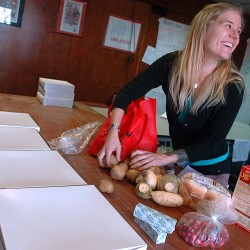 Willow Cortes-Eklund, Solidarity Harvest Coordinator, displays a selection of food provided to local families by Food AND Medicine and the Eastern Maine Labor Council.