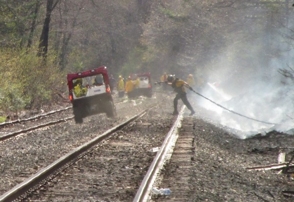 A firefighter drags hose from a tanker truck parked nearby, through a wooded area and onto an otherwise remote section of railroad tracks in Old Orchard Beach Thursday night.